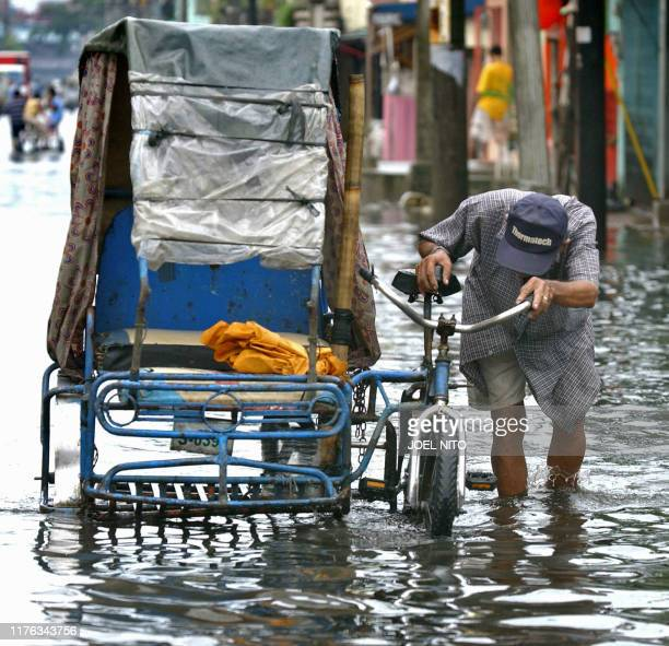 A resident makes their way through flooded streets in Malabon suburban Manila 30 October 2006 after powerful Typhoon Cimaron lashed the northern...
