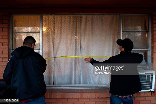 Resident measure the length of a window after it was blown out due to an explosion at a northwest Houston Texas manufacturing business on January 24...
