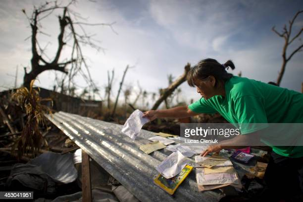 Resident Minda Amarilla dries documents she recovered after Typhoon Haiyan in heavily affected Barangay Mohon