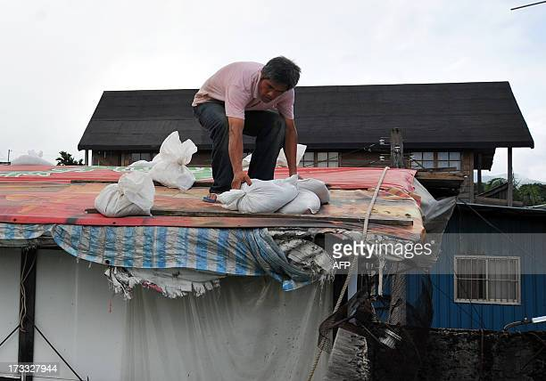 A resident moves stacks of sand bags on a roof to hold back flood waters as typhoon Soulik approaches northern Taiwan in New Taipei City on July 12...