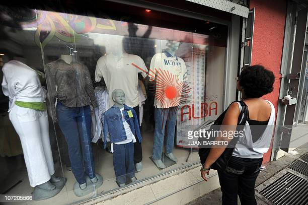 A resident observes the window of the ALBA store in Caracas on November 26 2010 AFP PHOTO/Juan BARRETO