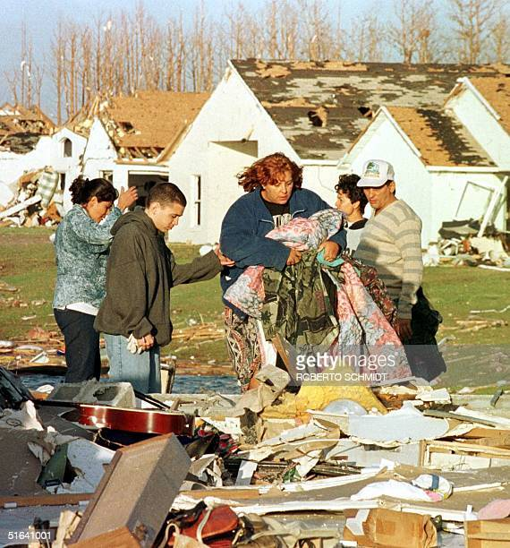 A resident of a Kissimmee Florida residential complex picks up some of her belongings from what is left of her home after a tornado leveled her house...