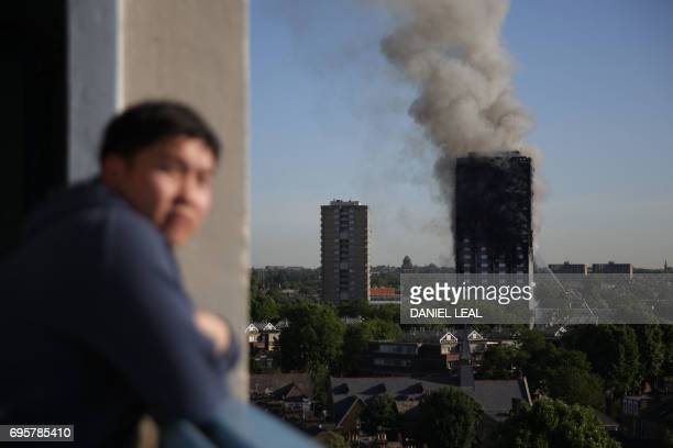 A resident of a nearby council estate watches smoke billowing from Grenfell Tower on June 14 2017 in west London The massive fire ripped through the...