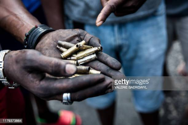 Resident of Delmas commune in Port-au-Prince shows bullet casings reportedly fired by armed people during a overnight clashes to remove barricades...
