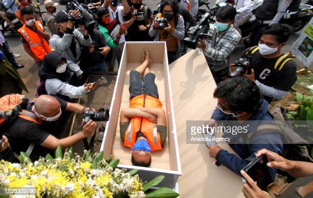 Resident of Jakarta is seen inside a coffin replica to contemplate as he caught not wearing as mask in Pasar Rebo, Jakarta, Indonesia on September 3,...