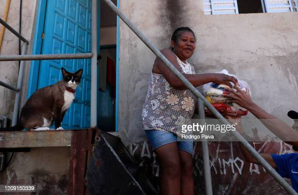 A resident of Jardim do Vale das Virtudes Favela receives a pack of food at Campo Limpo neighborhood on April 4 2020 in Sao Paulo Brazil According to...