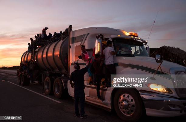 TOPSHOT A resident of La Blanca gives beverages to Honduran migrants taking part in a caravan heading to the US as they ride on a truck on their way...