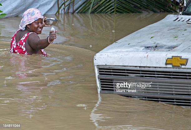 A resident of Leogane Haiti makes her way to her home as the water level continues to rise Friday October 26 2012 Residents of the Leogane have had...