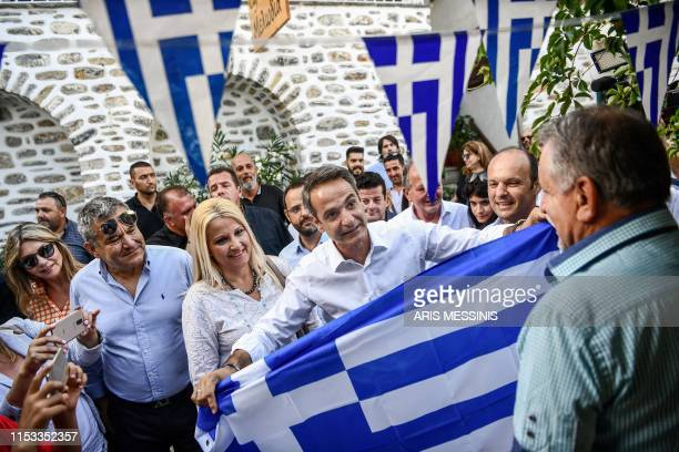 A resident of Makrynitsa offers a Greek National flag to Greece's opposition New Democracy leader Kyriakos Mitsotakis during his visit in the central...