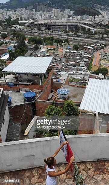 A resident of Mangueira shantytown hangs clothes to dry in a terrace in the Mangueira hill 2 km away from the Maracana stadium on December 17 2012 in...