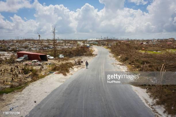 A resident of Marsh Harbour walks on a empty road on September 11 2019