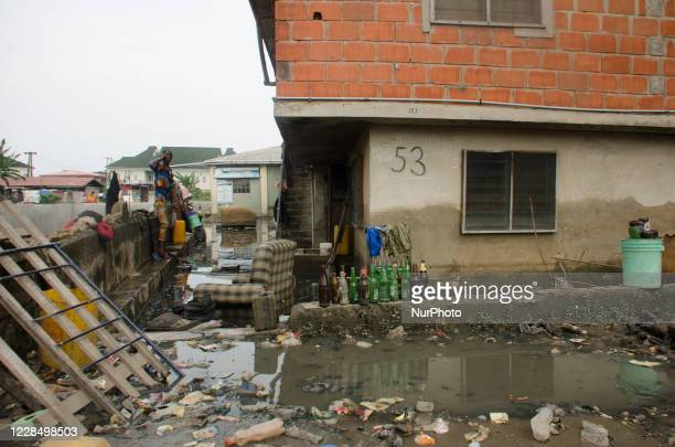 Resident of Oyebanjo Solarin Street in Ketu, Lagos make a phone call beside the drainage which washed away a two yet to be identified children, after...