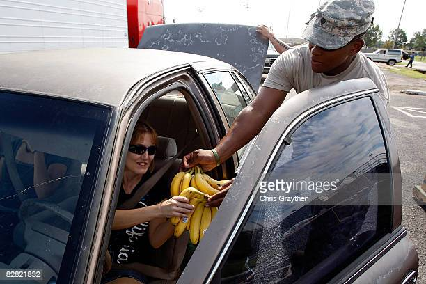 Resident of Pasadena, TX receives bannanas from a member of the Texas National Guard after being affected by Hurricane Ike September 15, 2008 in...