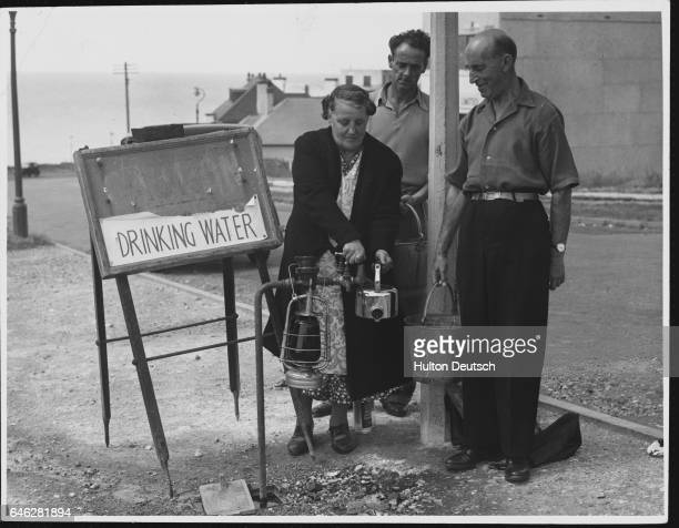 Resident of Saltdean fills a kettle with drinking water from a roadside pipe, set up during a water shortage.   Location: Saltdean, Sussex, England,...