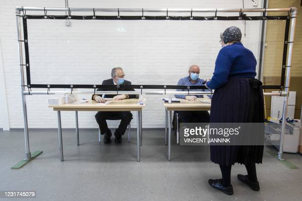Resident of Staphorstin traditional costume casts her vote in the parliamentary elections on the second day of the vote, on March 16, 2021. -...