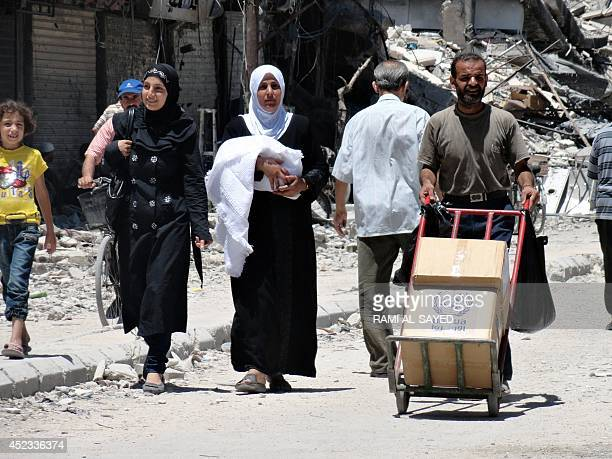 A resident of Syria's Yarmuk Palestinian refugee camp south of Damascus pushes a trolley loaded with a box of goods distributed by the United Nations...