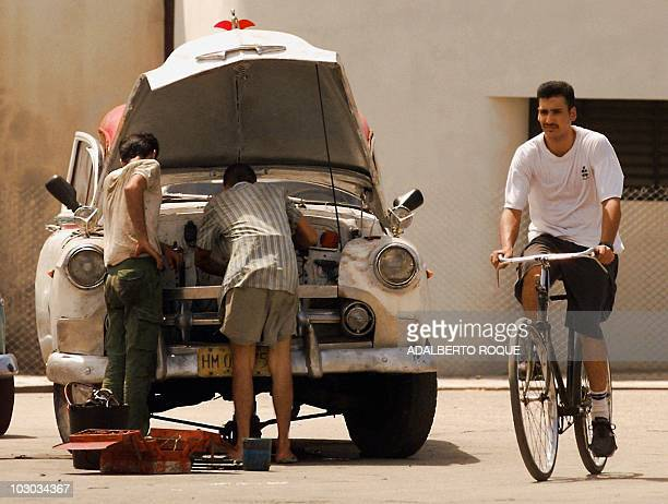 Resident of the Cuban capital rids his bike past two men working on the engine of a vintage 1949 Ford pickup truck in downtown Havana 03 September....