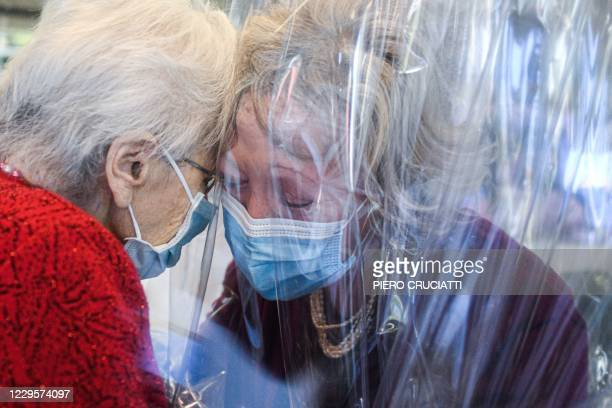 Resident of the Domenico Sartor nursing home in Castelfranco Veneto, near Venice, hugs her visiting daughter on November 11, 2020 through a plastic...