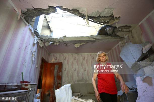 TOPSHOT A resident of the eastern Ukrainian city of Donetsk walks through her apartment building that was destroyed as a result of night shelling...