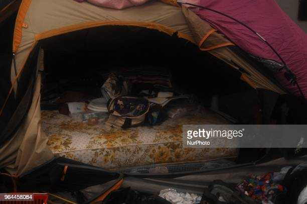 A resident of the encampment hurridly gathers her property onto the mattress she used as a bed in her tent including unused needles as the eviction...