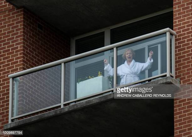 A resident of the Goodwin House senior living community dances on her balcony as she listens to the DC area motown band The Tribe play a social...