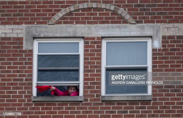 A resident of the Goodwin House senior living community waves a piece of cloth from her window as she listens to the DC area motown band The Tribe...