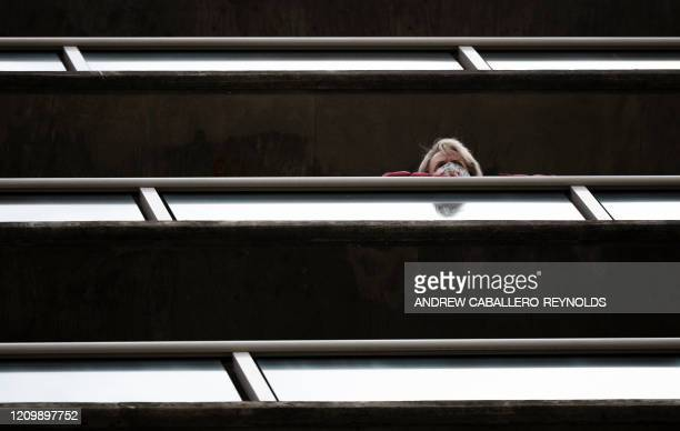 A resident of the Goodwin House senior living community wearing a mask looks on over a balcony as he listens to the DC area motown band The Tribe...