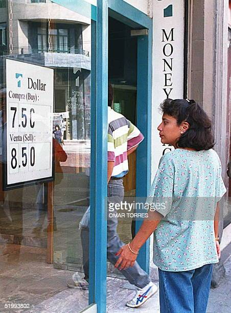 A resident of the Mexican capital cheks the new exchange rate for the US dollar at a local money exchange bureau 09 November as the peso continues...