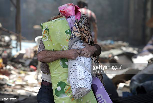 A resident of the Old City of Homs carries rolls of cloth out from a destroyed neighbourhood on May 12 2014 Syrians streamed back into the ruins of...