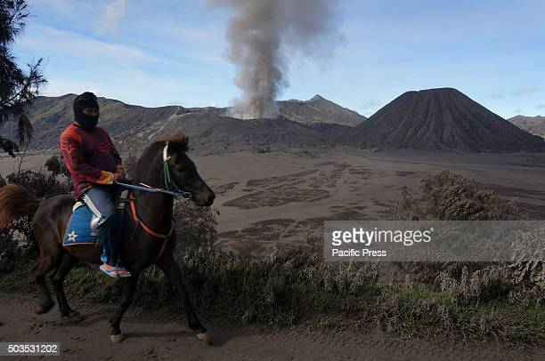 Resident of the Tenggerese rides a horse in the village of Cemoro where Mt Bromo is seen erupting The impact of the eruption affected the 24...