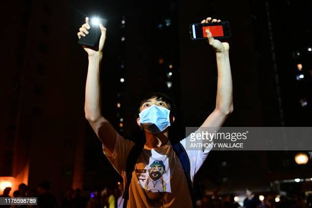 TOPSHOT A resident of the Tseung Kwan O area of Kowloon in Hong Kong holds up his phone flashlight as well as a phone displaying a Chinese Communist...