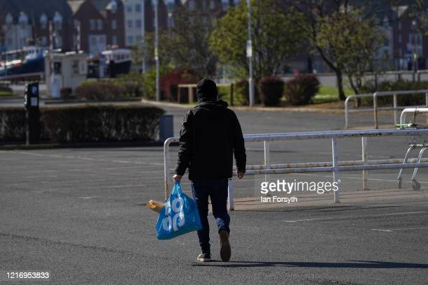 Resident of Whitby carries his shopping across an empty supermarket carpark during the Coronavirus pandemic lockdown on April 05, 2020 in Whitby,...