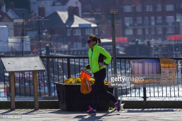 Resident of Whitby combines her run with a shopping trip as the streets of Whitby remain empty of visitors as they observe the guidelines during the...