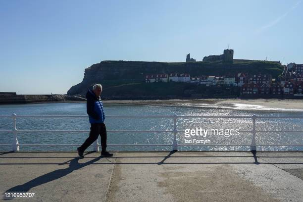 Resident of Whitby walks along the pier during a period of exercise as visitors observe the guidelines during the Coronavirus pandemic lockdown on...
