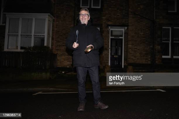 Resident on a street in Saltburn stands outside his home and takes part in the Clap for Heroes event on January 14, 2021 in Saltburn-by-the-Sea,...