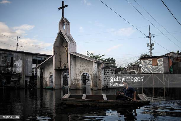 A resident paddles her makeshift boat past a chapel partially submerged in floodwaters at the Artex compound in Malabon city north of Manila...