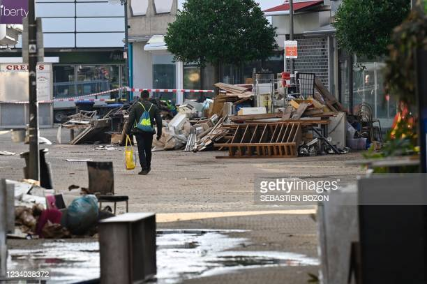 Resident passes a pile of debris in a street following heavy floods in Euskirchen, western Germany, on July 18, 2021. - The death toll from...
