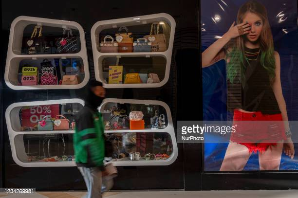 Resident passes in front of a closed outlet in a shopping center, Palu City, Central Sulawesi Province, Indonesia on July 28, 2021. To reduce the...