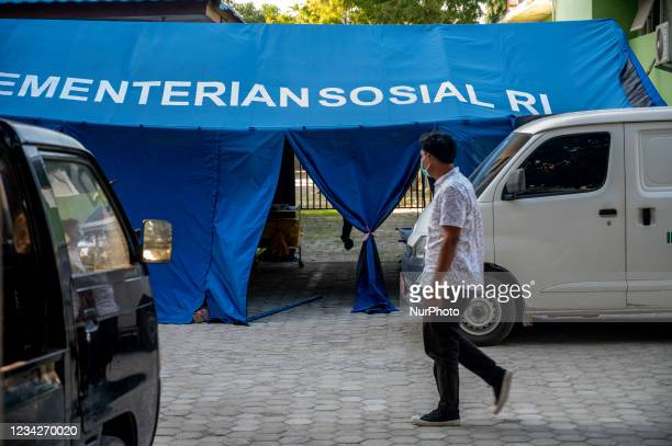 Resident passes in front of the emergency tent of Anutapura Hospital, Palu City, Central Sulawesi Province, Indonesia on July 28, 2021. To reduce the...