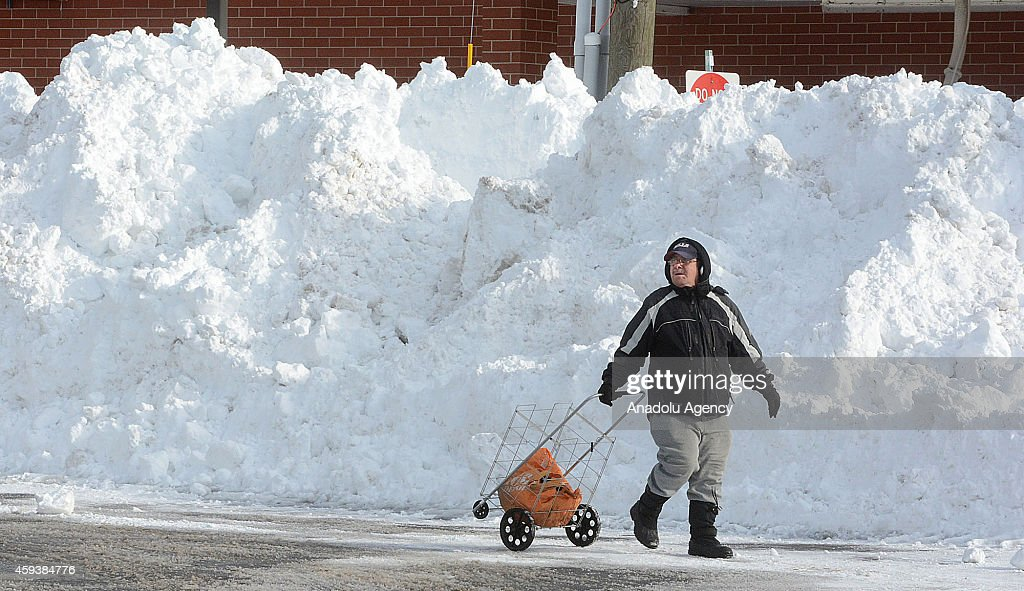 A resident passes near roadside snow on November 21, 2014 in Buffalo, New York as the death toll attributed to Buffalo snow rises to 13. A brutal blast of Arctic air triggered a lake-effect storm and snow in the states of New York, Ohio, Michigan, Wisconsin and Pennsylvania.