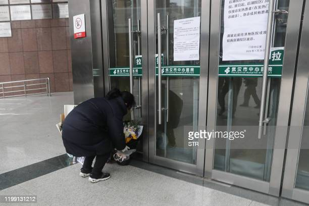 A resident places flowers for the late ophthalmologist Li Wenliang at the Houhu Branch of Wuhan Central Hospital in Wuhan in China's central Hubei...