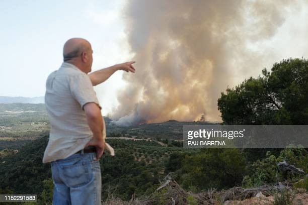 Resident points to a forest fire raging near Maials in the northeastern region of Catalonia on June 27, 2019. - A Spanish forest fire raged out of...
