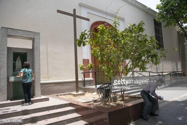 A resident prays outside of the San Pedro Church during Palm Sunday in Caracas Venezuela on Sunday April 5 2020 Amid the coronavirus as the world's...