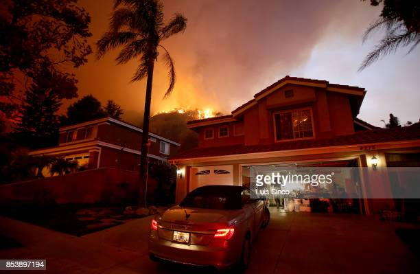 A resident prepares to evacuate as flames from the Canyon Fire burns in the hills surrounding a neighborhood on September 25 2017 in Corona...