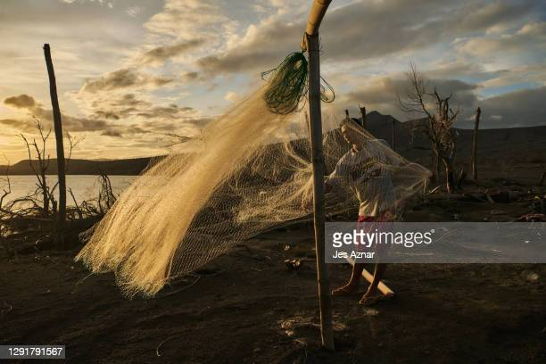 Resident preparing his net for fishing in the waters of the lake off the volcano island on December 15, 2020 in Balete, Batangas, Philippines. The...
