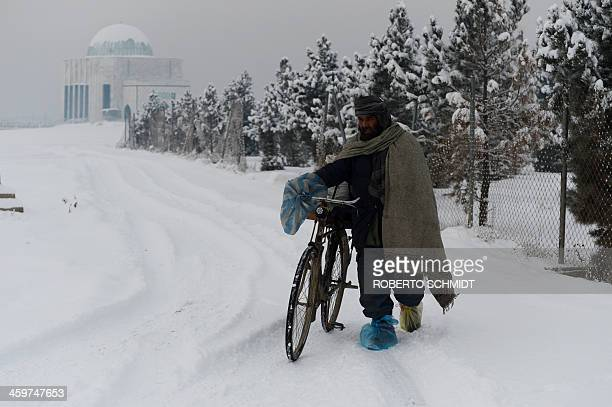 A resident pushes his bicycle along a snowcovered road in Kabul on December 30 2013 About two inches of snow fell overnight in Kabul marking the...
