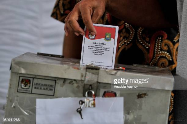 A resident puts ballot into the ballot box in Tangerang Indonesia on 27 June Today more than 152 million Indonesians elect the governors mayors and...