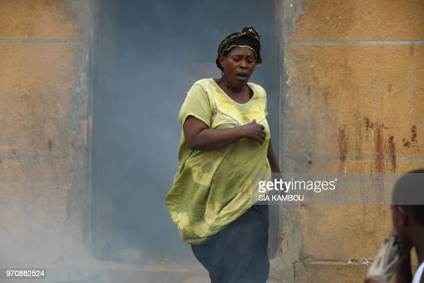 A resident reacts as agents of the National Institute of Public Hygene carry out fumigation in the Anyama district of Abidjan on June 9 as part of...