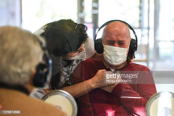 Resident reacts as he talks to his visiting sister at the Domenico Sartor nursing home in Castelfranco Veneto, near Venice, on November 11, 2020...