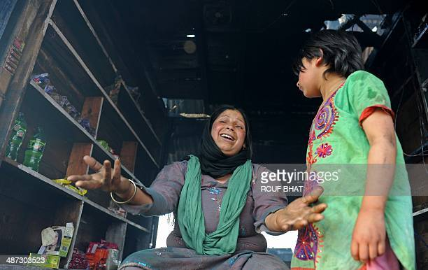 A resident reacts as she sits inside a damaged building after a fire broke out in a makeshift settlement in the Indian city of Srinagar on April 29...